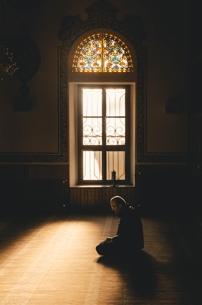 man kneeling while praying